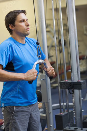 Man doing exercises in the gym on lat machine