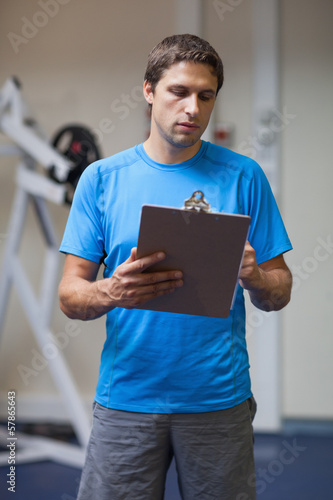 Serious personal trainer with clipboard in gym