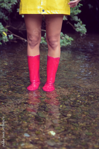 Low section of a woman in yellow raincoat and red gumboots in water