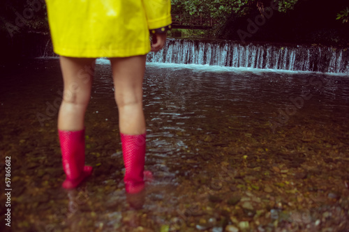 Woman in yellow raincoat and red gumboots in water