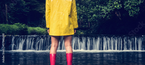 Woman in yellow raincoat and red gumboots looking at scenic waterfall