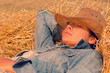 Beautiful woman in hat relaxing on hay with eyes closed