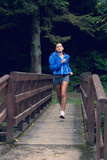 Healthy young woman jogging on footbridge