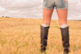 Mid section of woman in denim shorts and boots at cereal field