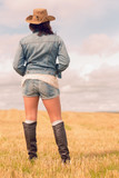 Rear view of woman in denim wear and boots at field