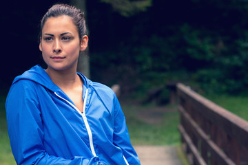 Thoughtful healthy young woman standing on footbridge