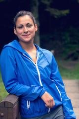 Portrait of smiling healthy woman standing on footbridge