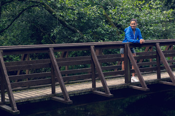 Smiling healthy young woman standing on footbridge