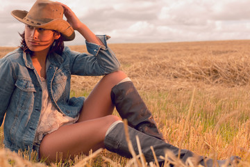 Beautiful young woman in hat sitting at cereal field