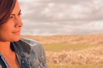 Close up of a beautiful young woman at cereal field