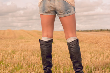 Mid section of a woman in denim shorts and boots at cereal field