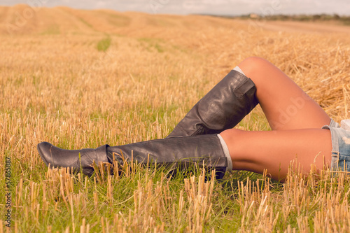 Low section of beautiful woman in boots relaxing at field