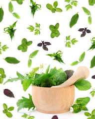 Herbs falling around mortar, isolated on white