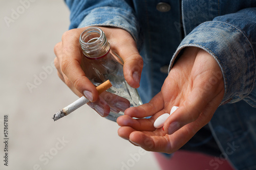 Girl holding vodka,pills and cigarettes