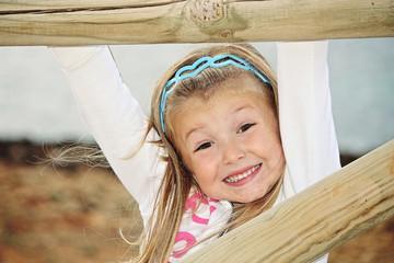 Bambina sorridente gioca dietro lo steccato