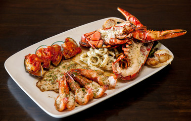 Grilled red lobster and seafood on platter.