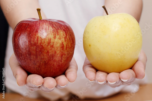Woman hands holding red and yellow apple