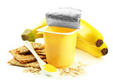 Tasty yogurt in open plastic cup, cookies and fruit, isolated