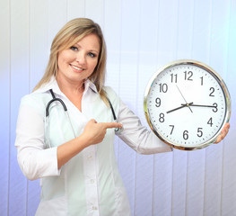 Young beautiful doctor with stethoscope and clock,