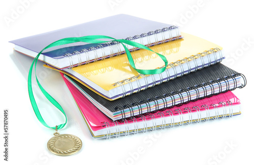 Medal for achievement in education and notebooks isolated
