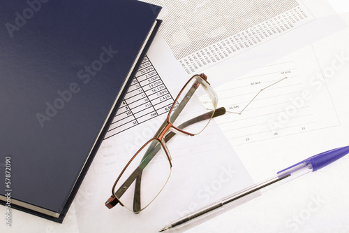 Business still-life of a pen, charts, glasses and diary