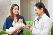 children's doctor examining newborn baby on mother's arms