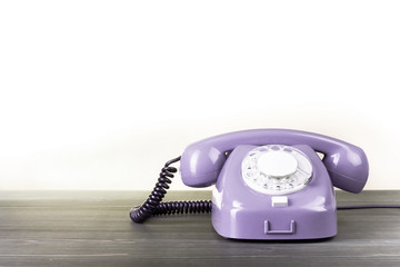 Retro violet telephone on table against white background