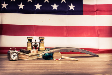 Binoculars, quill, clock, compass, glass, book front USA flag