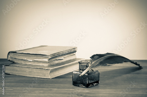 Quill pen, ink bottle, old books on table for vintage background