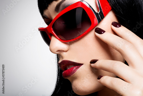 Face of a woman in red sunglasses with beautiful dark nails