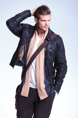 man in leather jacket is looking away to his side and smiles