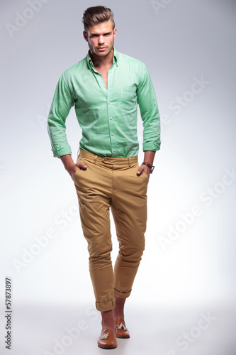 casual man walking toward the camera with hands in pockets