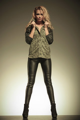 woman in leather pants posing by holding her collar