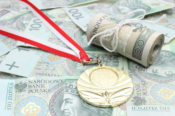 Gold medal and roll of tied banknotes on money background