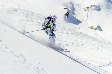 Skiing in the sunlight at high speed in a cloud of snow dust