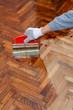 Home renovation varnishing oak parquet floor worker hand, brush