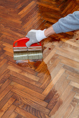 Home renovation varnishing oak parquet floor worker hand, brush