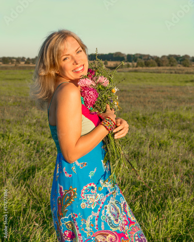 Woman with wild flowers smiling