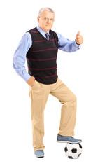 Senior gentleman with ball giving thumb up