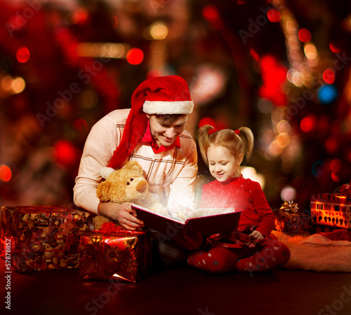 Christmas family reading book. Father and child open tale