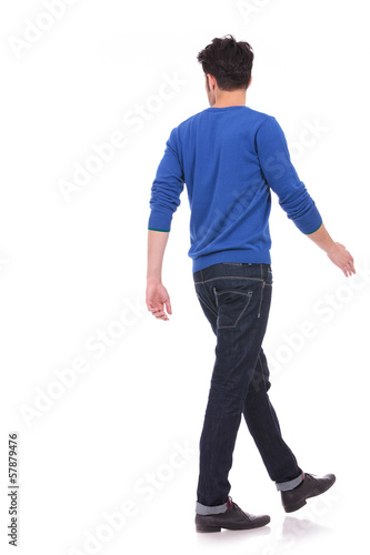back view of a walking casual man looking to a side