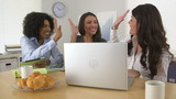 Three business women celebrating at good news while using laptop