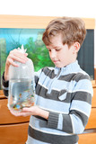 The boy holds packet with propical fish