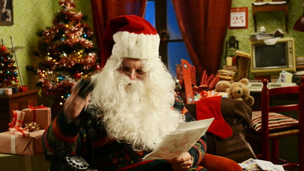 Santa Claus reading a letter and talking at phone