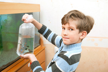 The boy is going to lets out fishes in an aquarium