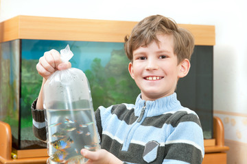 The boy holds parcel with aquarial fish