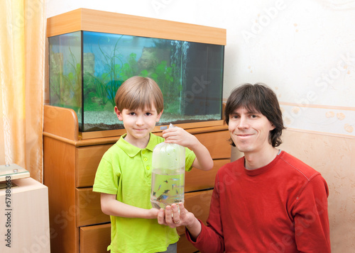 The boy and fater hold parcel with tropical fish