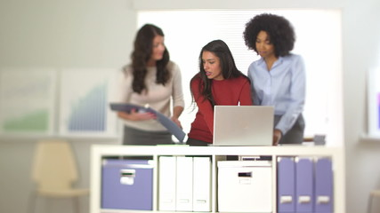 Hispanic business woman working at laptop with co workers