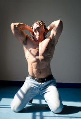 Muscleman kneeling shirtless with hands behind head, looking up