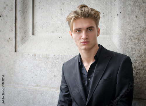 Attractive blond young man in jacket, against a wall